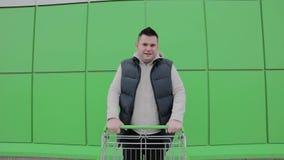 O homem tem o divertimento no shopping do estacionamento Passeios engraçados felizes do indivíduo no carrinho de compras Cliente  video estoque