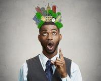 O homem tem a ideia, apontando o dedo que olha acima a cidade esboçada acima da cabeça Fotos de Stock Royalty Free