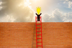 O homem tem a ideia que está sobre a escada sobre a parede de tijolo Imagens de Stock Royalty Free