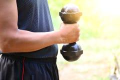 O homem tem uma barriga, gordura que guarda o peso preto do metal para o exercício Foto de Stock Royalty Free
