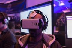 O homem tenta auriculares da engrenagem VR de Samsung da realidade virtual Imagens de Stock Royalty Free