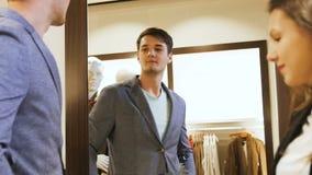 O homem tenta sobre Grey Jacket Looks no espelho na alameda vídeos de arquivo