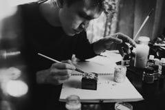 O homem tira pinturas em um papel Fotografia de Stock Royalty Free
