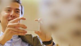 O homem toma a foto a pessoa ativa em Smartphone moderno vídeos de arquivo