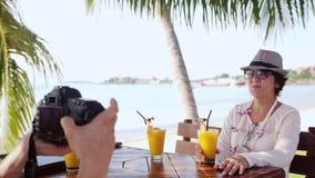 O homem toma a foto seu mum com a câmera no café exterior no recurso pela praia tropical 3840x2160 vídeos de arquivo