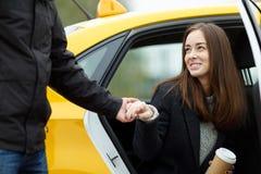 O homem toma a mão da mulher para ajudar a sair do táxi imagem de stock