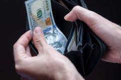 O homem toma o dinheiro de sua carteira Imagem de Stock Royalty Free