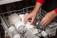 O homem toma pratos limpos na máquina de lavar louça Foto de Stock Royalty Free
