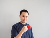 O homem toma um sorvo do café no copo vermelho Imagens de Stock Royalty Free