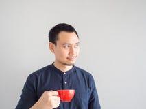 O homem toma um sorvo do café no copo vermelho Fotografia de Stock