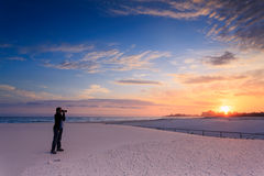 O homem toma uma fotografia do nascer do sol Imagens de Stock