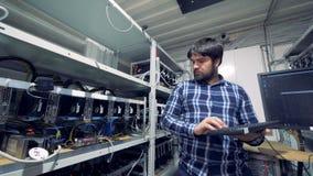 O homem trabalha com os computadores, minando cryptocurrencies