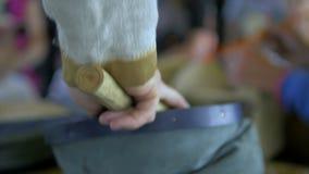 O homem trabalha com peles do ferreiro video estoque