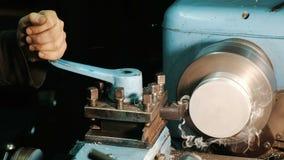 O homem trabalha em um torno, boleto de alumínio dos processos, microplaquetas do telit filme