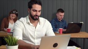 O homem trabalha no portátil video estoque