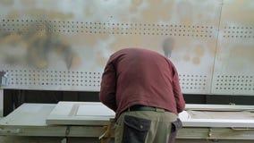 O homem, trabalhador remove a fita adesiva protetora produção de portas interiores da madeira filme