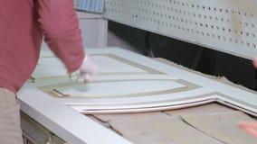 O homem, trabalhador remove a fita adesiva protetora produção de portas interiores da madeira vídeos de arquivo
