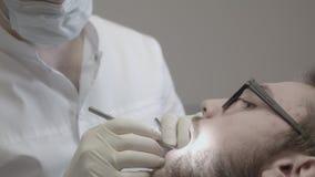 O homem trata os dentes no dentista video estoque