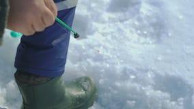 O homem trava peixes no lago do inverno video estoque