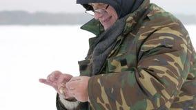 O homem travou um peixe pequeno na pesca do gelo Toma-o fora do gancho e dos lances ao gelo Vestido calorosamente em protetor filme