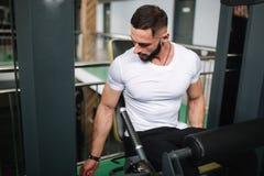 O homem treina os pés no gym Treinamento farpado considerável do halterofilista foto de stock royalty free