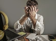 O homem triste e desesperado atrativo perde dentro a gravata que olha trabalho desarrumado e deprimido na mesa do laptop no PR do foto de stock