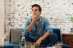 O homem triste que senta-se no café pensa a posse Chin Looking Imagem de Stock Royalty Free