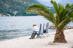 O homem triste senta-se na praia no dia da tempestade Louro de Kotor, Montenegro Fotos de Stock