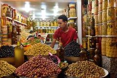 O homem troca azeitonas verdes em um mercado C4marraquexe, Marrocos Imagens de Stock