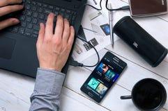 O homem usa a aplicação de Spotify Imagem de Stock Royalty Free