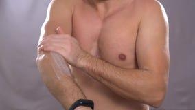 O homem usa o creme de corpo O homem asiático usa seus dedos para aplicar o creme branco em seu braço video estoque