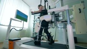 O homem usa o equipamento terapêutico em uma clínica Um paciente anda em uma trilha especial, usando uma prótese médica vídeos de arquivo