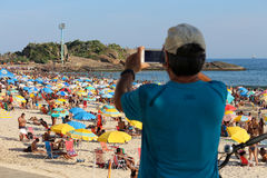 O homem usa o smartphone para fotografar a beleza da praia Imagens de Stock Royalty Free