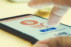 O homem usa o pagamento esperto do telefone com bitcoin Imagens de Stock