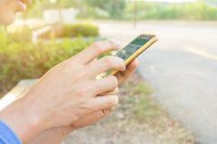 O homem usa seu telefone celular exterior, ascendente próximo Fotos de Stock