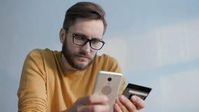 O homem usa o telefone celular comprando na loja em linha filme