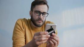 O homem usa o telefone celular comprando na loja em linha vídeos de arquivo