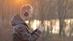 O homem usa o telefone no parque vídeos de arquivo