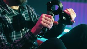 O homem usa um controlador, manches ao jogar um jogo do vr em um capacete da realidade virtual video estoque