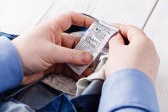 O homem vê a instrução de cuidado de lavagem em calças de brim Foto de Stock Royalty Free