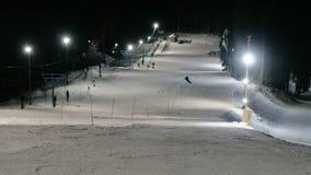 O homem vai abaixo da montanha em uma inclinação do esqui da montanha ao lado do elevador na noite vídeos de arquivo