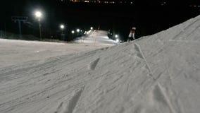 O homem vai abaixo da montanha em uma inclinação do snowboard ao lado do elevador Snowboarding da noite video estoque