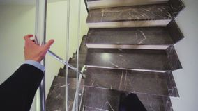 O homem vai acima das escadas decoradas com headcam de mármore da telha video estoque