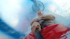 O homem vai em uma corrediça de água fechado Imagens de Stock