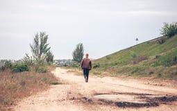 O homem vai em uma estrada de terra Fotos de Stock Royalty Free