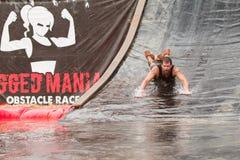 O homem vai Headfirst abaixo da corrediça de água na raça do curso de obstáculo fotografia de stock royalty free