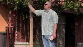 O homem verifica a árvore de maçã em casa video estoque