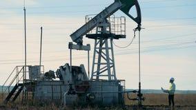 O homem verifica trabalhos de uma torre de óleo, bomba de óleo filme