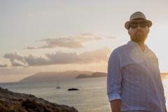 o homem Vermelho-farpado da aparência europeia nos raios dourados do sol está no alvorecer contra o contexto do mar e das ilhas fotografia de stock