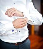 O homem veste botão de punho em uma luva da camisa Um noivo que põe sobre botão de punho como obtém vestido no vestuário formal T Imagens de Stock